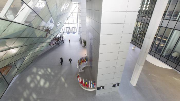 Vistors walk through the entrance hall inside the new headquarters of the European Central Bank (ECB) in Frankfurt, Germany, on Friday, Feb. 13, 2015. The ECB's plan to buy at least 1.1 trillion euros of bonds to boost inflation across the currency union is shielding the bloc's other debtor nations during the latest phase of the Greek crisis. Photographer: Martin Leissl/Bloomberg