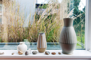 Denby and Poole pottery with beach pebbles on a shelf