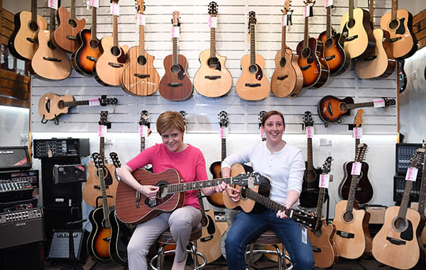 PAISLEY, SCOTLAND - JUNE 02: SNP leader Nicola Sturgeon and MP for Paisley and Renfrewshire South Mhairi Black play guitars in a shop while campaigning for the General Election on Wellmeadow Street on June 2, 2017 in Paisley, Scotland. Polls are showing the SNP out in front and the Conservatives set to close in on Labour as the general election approaches next week. (Photo by Jeff J Mitchell/Getty Images)