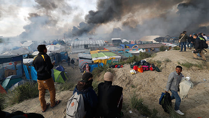 Smoke rises the sky as migrants and journalists look at burning makeshift shelters and tents in the