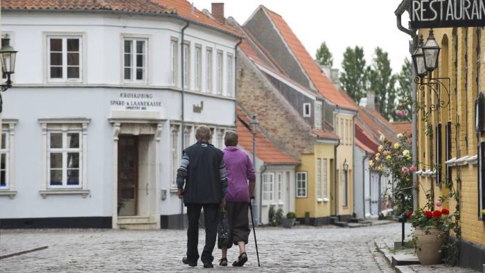 An elderly couple walks along a street in downtown Aeroeskoebing, Denmark