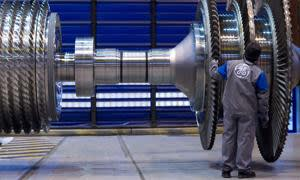 A General Electric Co. employee examines a component for a gas turbine at the company's factory in Belfort, France, on Tuesday, Dec. 14, 2010. General Electric Co. said sales may increase as much as 5 percent next year as its industrial divisions return to growth and profit climbs. Photographer: Fabrice Dimier/Bloomberg