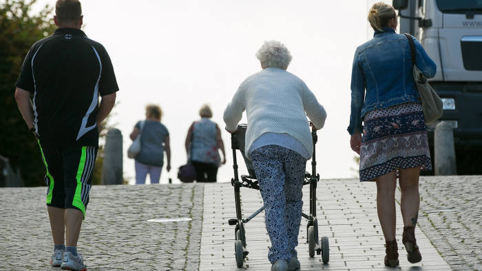 A pensioner, center, uses a walking frame in Sellin, Ruegen Island, Germany, on Saturday, Aug. 27, 2016. Germany's Bundesbank said raising the legal retirement age to 69 by 2060 could ease some of the pressure on the country's state pension system as the population ages. Photographer: Krisztian Bocsi/Bloomberg
