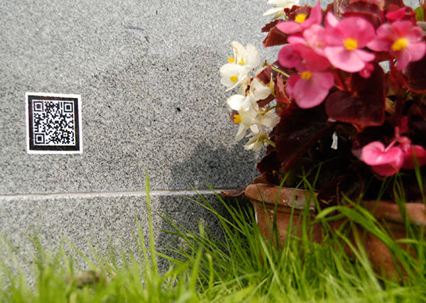 A gravestone with a 'QR code', which can be scanned to upload data about the deceased