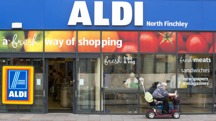 A woman using a motorized cart, sits outside the entrance to an Aldi supermarket store in London, U.K., on Monday, June 29, 2015. The growth of Aldi and fellow German-owned discounter Lidl has changed the British grocery landscape over the last five years. Photographer: Jason Alden/Bloomberg