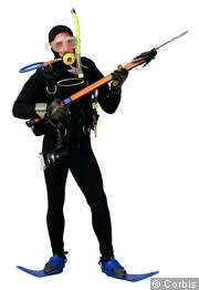 A scuba diver standing and showing off his equipment
