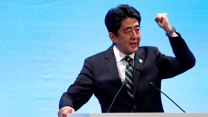 Japanese Prime Minister Shinzo Abe raises a fist as he makes a speech