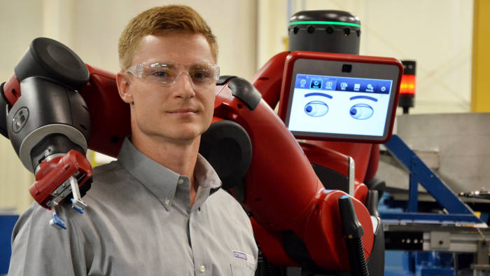 Mechanical engineer Jesse Rochelle works with a Robot called Baxter which automates production at the Stenner Pumps factory Thursday April 21, 2016 in Jacksonville, Florida.