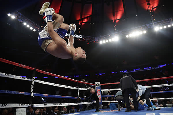 Teofimo Lopez, left, celebrates after knocking down Ronald Rivas during the second round of a lightweight boxing match Saturday, May 20, 2017, in New York. Lopez stopped Rivas in the second round. (AP Photo/Frank Franklin II)
