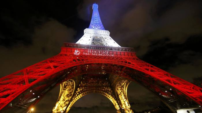 """The Eiffel Tower is lit with the blue, white and red colours of the French flag in Paris, France, November 17, 2015, to pay tribute to the victims of a series of deadly attacks on Friday in the French capital. The City of Paris motto """"Fluctuat Nec Mergitur"""", Latin for """"buffeted (by waves) but not sunk"""" is projected on the Eiffel Tower. REUTERS/Jacky Naegelen TPX IMAGES OF THE DAY"""