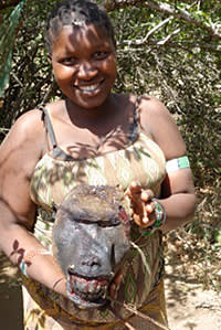 A Hadza woman holds a baboon's head
