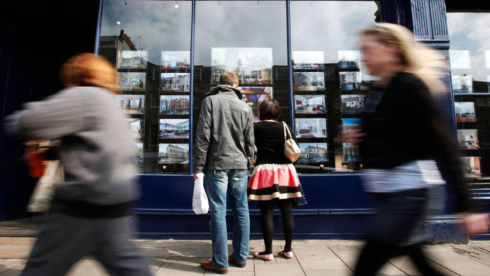 A couple look at properties advertised in an estate agent's window in London, U.K., on Sunday, April 19, 2009. Chancellor of the Exchequer Alistair Darling will set aside 1 billion pounds ($1.45 billion) to revive house building in the U.K., a person familiar with the matter said, after the financial crisis slashed the number of construction projects in half in the last year. Photographer: Jason Alden/Bloomberg News