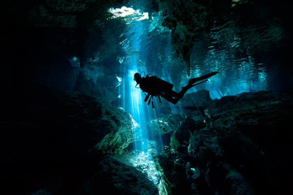 A diver in one of Tulum's cenotes