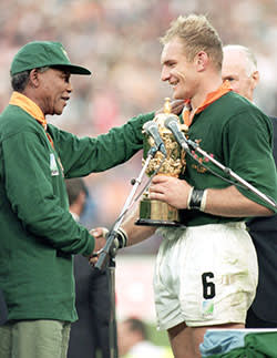 Francois Pienaar of South Africa receives the William Webb Ellis Trophy from President Nelson Mandela after the Rugby World Cup final between South Africa and New Zealand held on June 24, 1995 at Ellis Park in Johannesburg, South Africa. South Africa won the match 15-12.