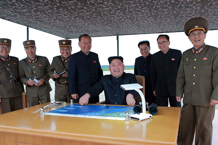 """TOPSHOT - CORRECTION - This picture from North Korea's official Korean Central News Agency (KCNA) taken on August 29, 2017 and released on August 30, 2017 shows North Korean leader Kim Jong-Un (C) watching the launch of an intermediate-range strategic ballistic rocket Hwasong-12 at an undisclosed location near Pyongyang. Nuclear-armed North Korea said on August 30 that it had fired a missile over Japan the previous day, the first time it has ever acknowledged doing so. / AFP PHOTO / KCNA VIA KNS / STR / South Korea OUT / REPUBLIC OF KOREA OUT ---EDITORS NOTE--- RESTRICTED TO EDITORIAL USE - MANDATORY CREDIT """"AFP PHOTO/KCNA VIA KNS"""" - NO MARKETING NO ADVERTISING CAMPAIGNS - DISTRIBUTED AS A SERVICE TO CLIENTS THIS PICTURE WAS MADE AVAILABLE BY A THIRD PARTY. AFP CAN NOT INDEPENDENTLY VERIFY THE AUTHENTICITY, LOCATION, DATE AND CONTENT OF THIS IMAGE. THIS PHOTO IS DISTRIBUTED EXACTLY AS RECEIVED BY AFP. / The erroneous mention[s] appearing in the metadata of this photo by STR has been modified in AFP systems in the following manner: [at an undisclosed location near Pyongyang] instead of [in Pyongyang]. Please immediately remove the erroneous mention[s] from all your online services and delete it (them) from your servers. If you have been authorized by AFP to distribute it (them) to third parties, please ensure that the same actions are carried out by them. Failure to promptly comply with these instructions will entail liability on your part for any continued or post notification usage. Therefore we thank you very much for all your attention and prompt action. We are sorry for the inconvenience this notification may cause and remain at your disposal for any further information you may require.STR/AFP/Getty Images"""