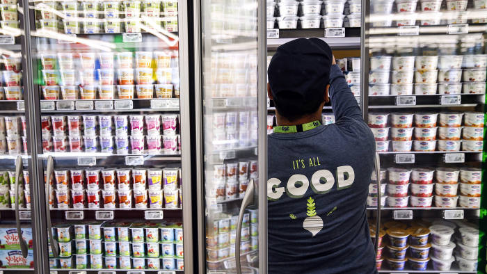 An employee stocks yogurt for sale on the opening day of the 365 by Whole Foods Market store in the Silver Lake neighborhood of Los Angeles, California, U.S., on Wednesday, May 25, 2016
