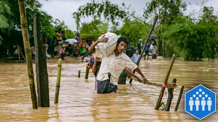 COX'S BAZAR, BANGLADESH - SEPTEMBER 19: Refugees cross a flooded bridge in the Balukhali Rohingya refugee camp on September 19, 2017 in Cox's Bazar, Bangladesh. Over 400,000 Rohingya refugees have fled into Bangladesh since late August during the outbreak of violence in the Rakhine state as Myanmar's de facto leader Aung San Suu Kyi broke her silence on the Rohingya crisis on Tuesday and defended the security forces while criticism on her handling of the Rohingya crisis grows. Recent satellite images released by Amnesty International provided evidence that security forces were trying to push the minority Muslim group out of the country. (Photo by Allison Joyce/Getty Images)