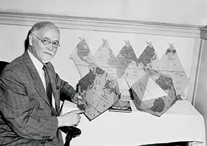 Professor Irving Fisher of Yale University, internationally famous economist, is shown  in New York, June 9, 1944.  He has devised a two-way map that may be folded into a globe or spread flat. Here, Prof. Fisher demonstrates the two uses or his novel map