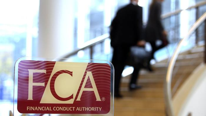 Visitors walk up a staircase as a logo sits on a sign in the reception area of the Financial Conduct Authority