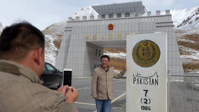 To go with story 'Pakistan-China-economy-transport, FEATURE' by Guillaume LAVALLÉE In this photograph taken on September 29, 2015, a Chinese national takes a photograph of his colleague at the Pak-China Khunjerab Pass, the world's highest paved border crossing at 4,600 metres above sea level.  A glossy highway and hundreds of lorries transporting Chinese workers by the thousands: the new Silk Road is under construction in northern Pakistan, but locals living on the border are yet to be convinced they will receive more from it than dust.    AFP PHOTO / Aamir QURESHI        (Photo credit should read AAMIR QURESHI/AFP/Getty Images)