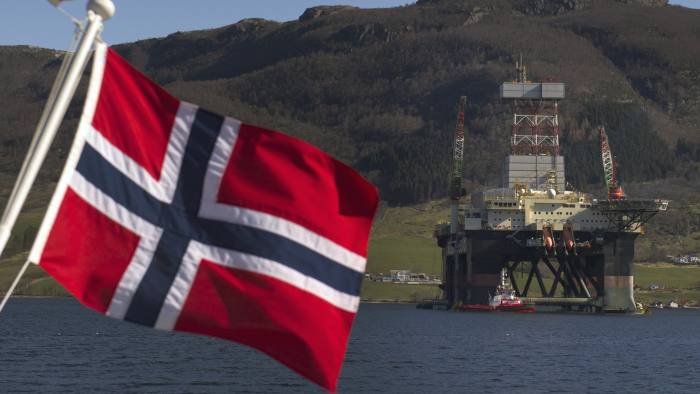 The New Scarabeo 8 Ultra Deepwater Oil Rig...A Norwegian national flag flies from a vessel near the Scarabeo 8 deepwater oil drilling rig, operated by ENI Norge AS, in Olensvag, Norway, on Tuesday, April 3, 2012. The world's seventh-largest oil exporter boasts no net debt, adding to its appeal as an alternative to the debt-riddled euro area. Photographer: Kristian Helgesen/Bloomberg