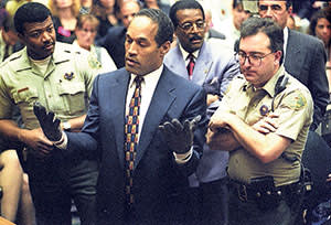 OJ Simpson tries on a pair of bloody gloves at the prosecution's request during his trial in 1995