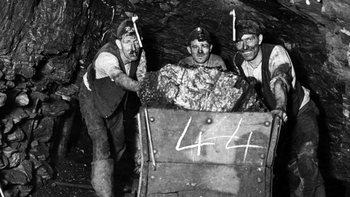 circa 1960: Three miners push a load of coal through the tunnel at Bromley pit in Pensford, Surrey. (Photo by Fox Photos/Getty Images)