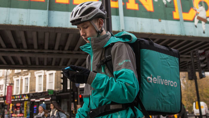 Restaurant Food Delivery company 'Deliveroo' employee, Billy Shannon looks for an address while working in Camden Town, north London in November 17, 2016.