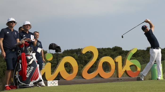 2016 Rio Olympics - Golf - Preliminary - Training session - Olympic Golf Course - Rio de Janeiro, Brazil 09/08/2016. Justin Rose (GBR) of Great Britain hits a tee shot as compatriot Danny Willett looks on during practice session. REUTERS/Andrew Boyers FOR EDITORIAL USE ONLY. NOT FOR SALE FOR MARKETING OR ADVERTISING CAMPAIGNS.