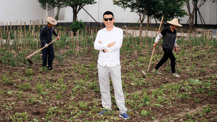Zhou Chengjian poses in vegetable fields, a reconstruction of his home village, outside his Shanghai HQ
