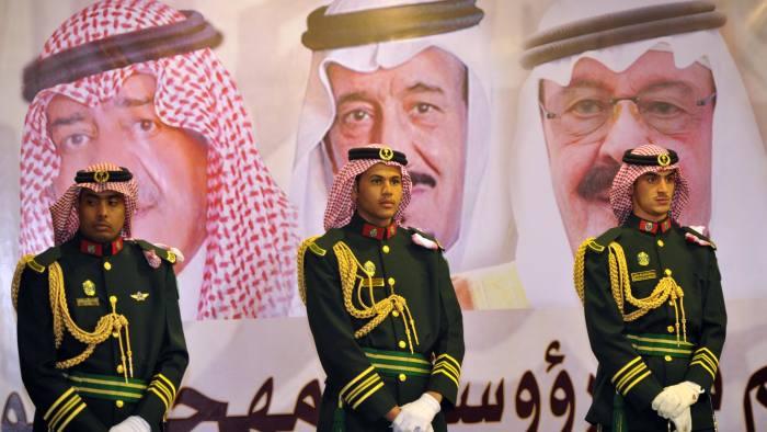 Saudi royal guards stand on duty in front of portraits of King Abdullah bin Abdulaziz (R), Crown Prince Salman bin Abdulaziz (C) and second deputy Prime Minister Mugren bin Abdulaziz