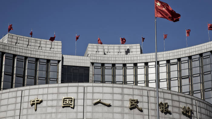 A Chinese national flag flies above the People's Bank of China (PBOC) headquarters in Beijing, China, on Monday, March 7, 2016. Chinese small-cap stocks rallied after Premier Li Keqiang failed to mention a planned shift to a more market-based system for initial public offerings, a reform seen luring funds from existing equities. Photographer: Qilai Shen/Bloomberg