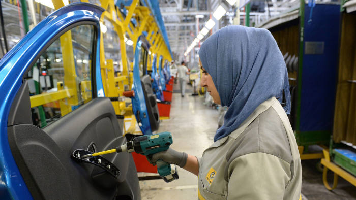 An employee of the French Renault group in Morocco works on a production line at the Renault factory of Melloussa, near Tangier, on April 23, 2014
