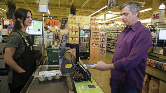 In this photo taken Friday, Oct. 17, 2014, Eddy Cue, right, Apple Senior Vice President of Internet Software and Services, demonstrates the new Apple Pay mobile payment system at a Whole Foods store in Cupertino, Calif. The new system launches on Monday. (AP Photo/Eric Risberg)