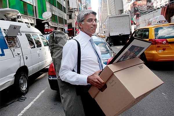 An employee of Lehman Brothers Holdings Inc. carries a box out of the company's headquarters building (background) September 15, 2008 in New York City