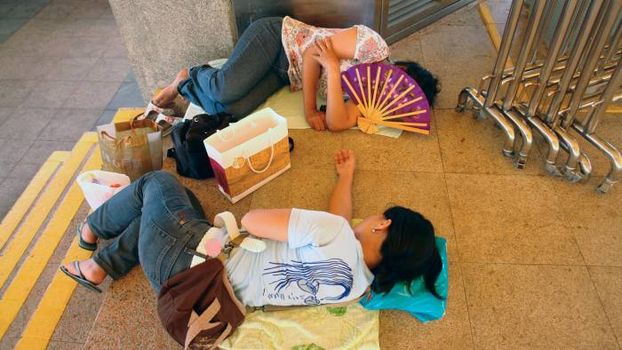 Domestic helpers take a rest in Hong Kong. Higher salaries are tempting them into illegal work on the mainland