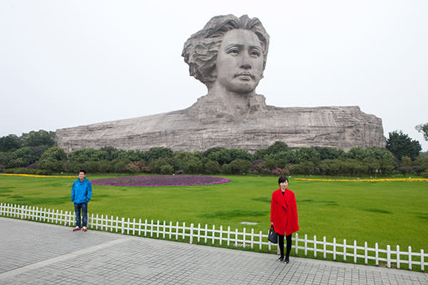 Two tourists pose for a photograph in front of a statue of the young Mao Zedong in the Changsha, Hunan province