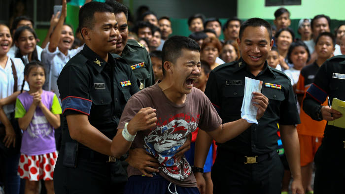 A young man (C) reacts after being exempted from military service during an army draft held at a school in Klong Toey, the dockside slum area in Bangkok, Thailand, April 5, 2017. Picture taken April 5, 2017. REUTERS/Athit Perawongmetha     TPX IMAGES OF THE DAY
