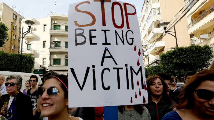 "Women, one holding a placard, take part in a rally, notably to denounce domestic violence, on the ""International Women's Day"" on March 8, 2014 in front of the National Museum in the capital Beirut"