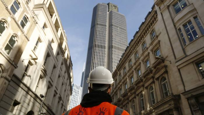 A construction worker looks on toward skyscraper Tower 42, in the City of London, U.K. on Wednesday, Nov. 2, 2016. Most U.K. bankers believe London will remain Europe's pre-eminent financial center after Brexit, according to consulting firm Synechron Inc. Photographer: Luke MacGregor/Bloomberg