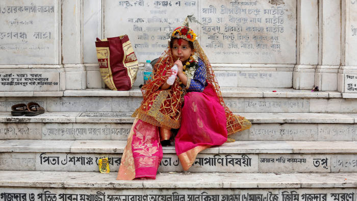 A girl dressed as Kumari, drinks as she sits on stairs after attending rituals to celebrate the Navratri Festival inside the Adyapeath Temple, on the outskirts of Kolkata, India April 5, 2017. REUTERS/Rupak De Chowdhuri