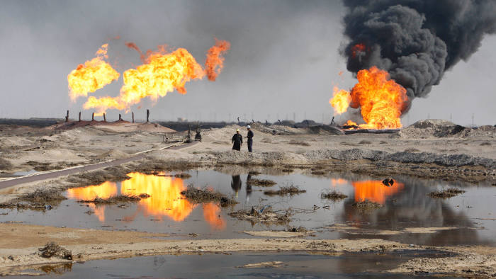 Excess gas is burned off near workers at the Rumala oil field, south of Basra, 420 km (260 miles) southeast of Baghdad, December 2, 2009