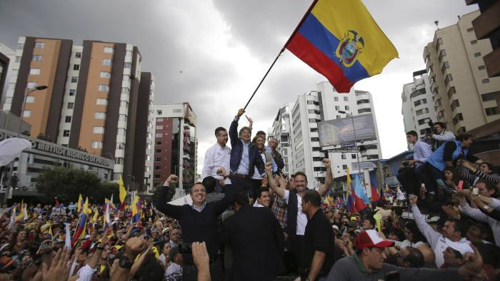 CREO's presidential candidate Guillermo Lasso waves an Ecuadorean national flag, accompanied by his wife Maria de Lourdes Alcivar, his running mate Andres Paez, and surrounded by supporters outside the Electoral National Council, in Quito, Ecuador, Tuesday, Feb. 21, 2017. The Andean country is headed to a presidential runoff as ruling party candidate Lenin Moreno faces off against Lasso, a conservative former banker. (AP Photo/Dolores Ochoa)