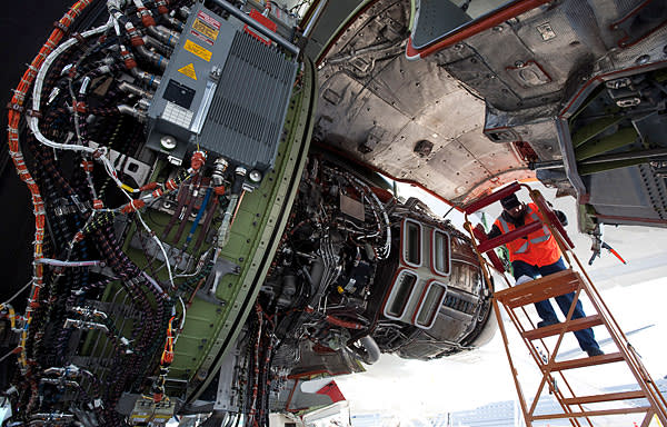 Boeing flight line mechanic Mike Feeney work on an engine of a Boeing 747-8 freighter