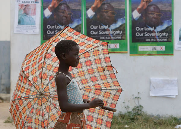 A child walks past election posters in Harare, Zimbabwe, in 2008