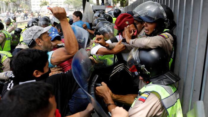 Demonstrators scuffle with security forces during an opposition rally in Caracas, Venezuela