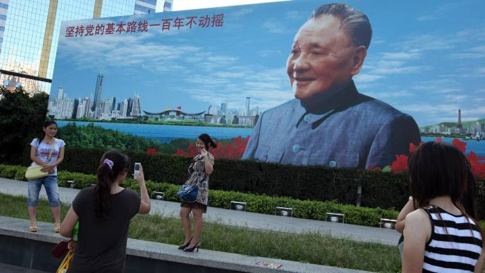 People pose for photos in front of a billboard to Deng Xiaoping in Shenzhen, China July 4, 2010. The former Chinese leader's economic reforms turned Shenzhen into the country's first Special Economic Zone. Photo by Doug Kanter