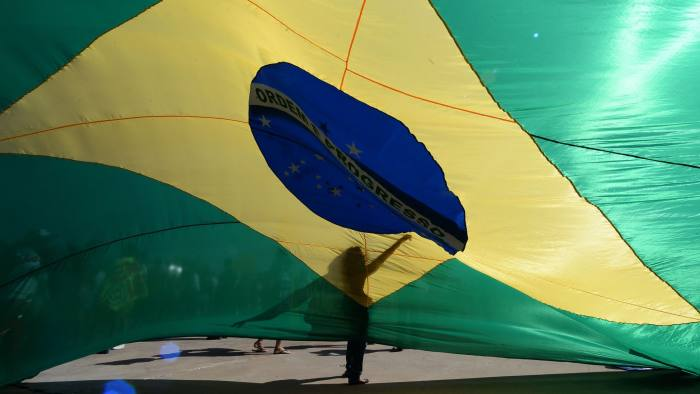TOPSHOT - A supporter of Brazil's impeached president Dilma Rousseff demonstrates against President Michel Temer next to a huge Brazilan flag in Brasilia on September 7, 2016. Brazil's impeached president Dilma Rousseff left the official presidential residence for the last time yesterday, flying to her coastal hometown as Temer jetted home from the G20 summit in China. Symbolically marking the end of an era of 13 years in power for the leftist Workers' Party, Rousseff stepped out of the Alvorada Palace and into the blazing Brasilia sunshine, surrounded by some 100 supporters, former ministers and allied lawmakers.  / AFP / ANDRESSA ANHOLETE        (Photo credit should read ANDRESSA ANHOLETE/AFP/Getty Images)