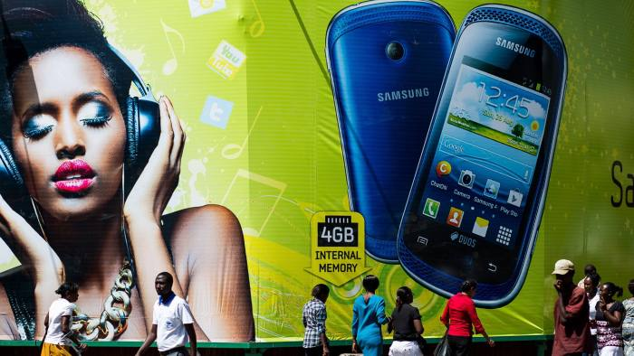 General Economy Ahead Of The Kenyan Elections...Pedestrians pass a giant advertisement for Samsung Electronics Co. mobile phones in Nairobi, Kenya, on Friday, March 1, 2013. Next week's presidential vote will be the first since disputed elections in 2007 triggered ethnic fighting in which more than 1,100 people died and another 350,000 fled their homes. Photographer: Trevor Snapp/Bloomberg