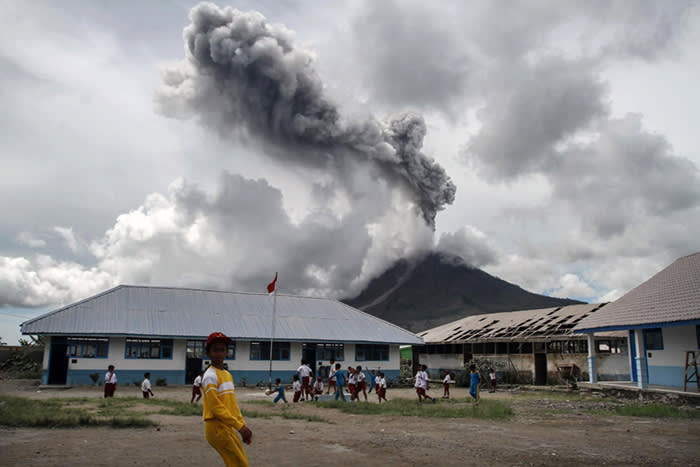 TOPSHOT - Children play at an elementary school as the Mount Sinabung volcano spews smoke in Karo on November 13, 2017. Sinabung roared back to life in 2010 for the first time in 400 years, after another period of inactivity it erupted once more in 2013, and has remained highly active since. / AFP PHOTO / Ivan DAMANIKIVAN DAMANIK/AFP/Getty Images